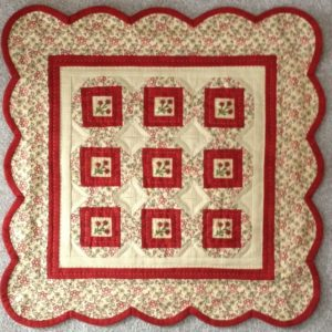 """Little Red Ten is 16"""" x 16"""" and has those cute little red flower buttons in the center of each block. The buttons are included in the pattern. The kit includes the fabrics for the top, back, and binding along with the pattern"""