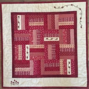 """Little Red Three is a good beginner's project with simple rail fence blocks. It requires some basic hand embroidery and it is 17"""" square. The flowers are tiny (about 1/4"""") red buttons. The pattern includes the packet of red flower-shaped buttons."""