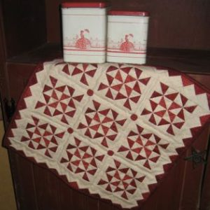 """Little Red 4 This 17 1/2"""" square wall hanging or table topper features prairie points around the outside edge. Kit includes the pattern, fabrics for the top and binding, and the four red buttons."""