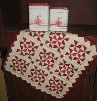"Little Red 4 This 17 1/2"" square wall hanging or table topper features prairie points around the outside edge. Kit includes the pattern, fabrics for the top and binding, and the four red buttons."