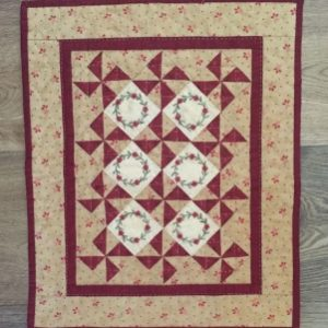 """Little Red Five finishes at 13"""" x 15 1/2"""". It features pinwheel blocks set on point and little embroidered wreaths with red flower buttons."""
