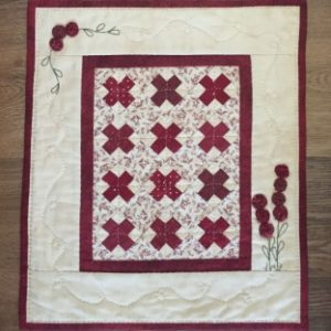 "This Little Red is simply pieced, has a bit of embroidery, and little yo-yos that form the flowers. It is just 12"" x 14"". The kit includes all the fabrics needed for the top and binding, as well as the backing fabric and pattern."