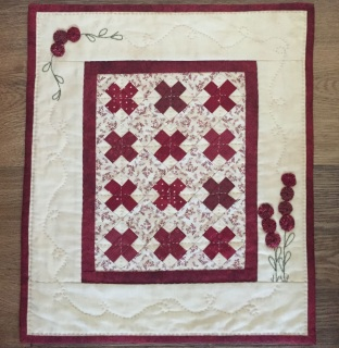 """This Little Red is simply pieced, has a bit of embroidery, and little yo-yos that form the flowers. It is just 12"""" x 14"""". The kit includes all the fabrics needed for the top and binding, as well as the backing fabric and pattern."""